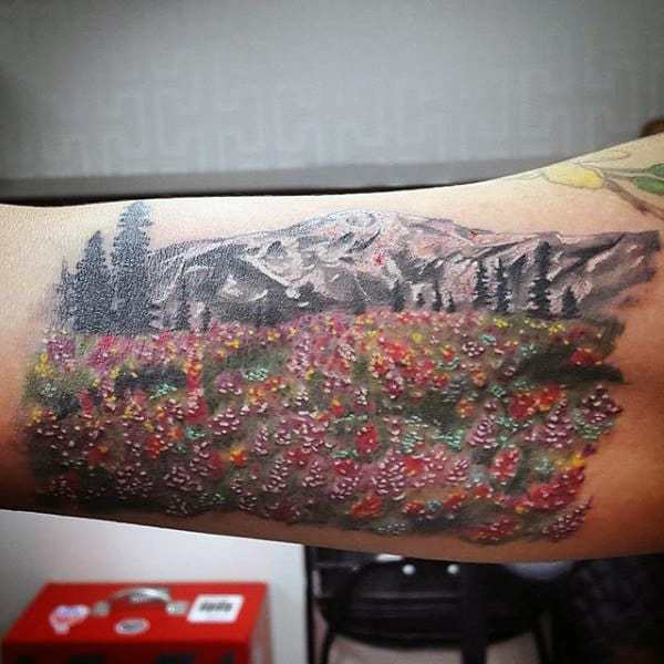 Colorful Classic Flower Field And Mountains Forearm Tattoo On Male