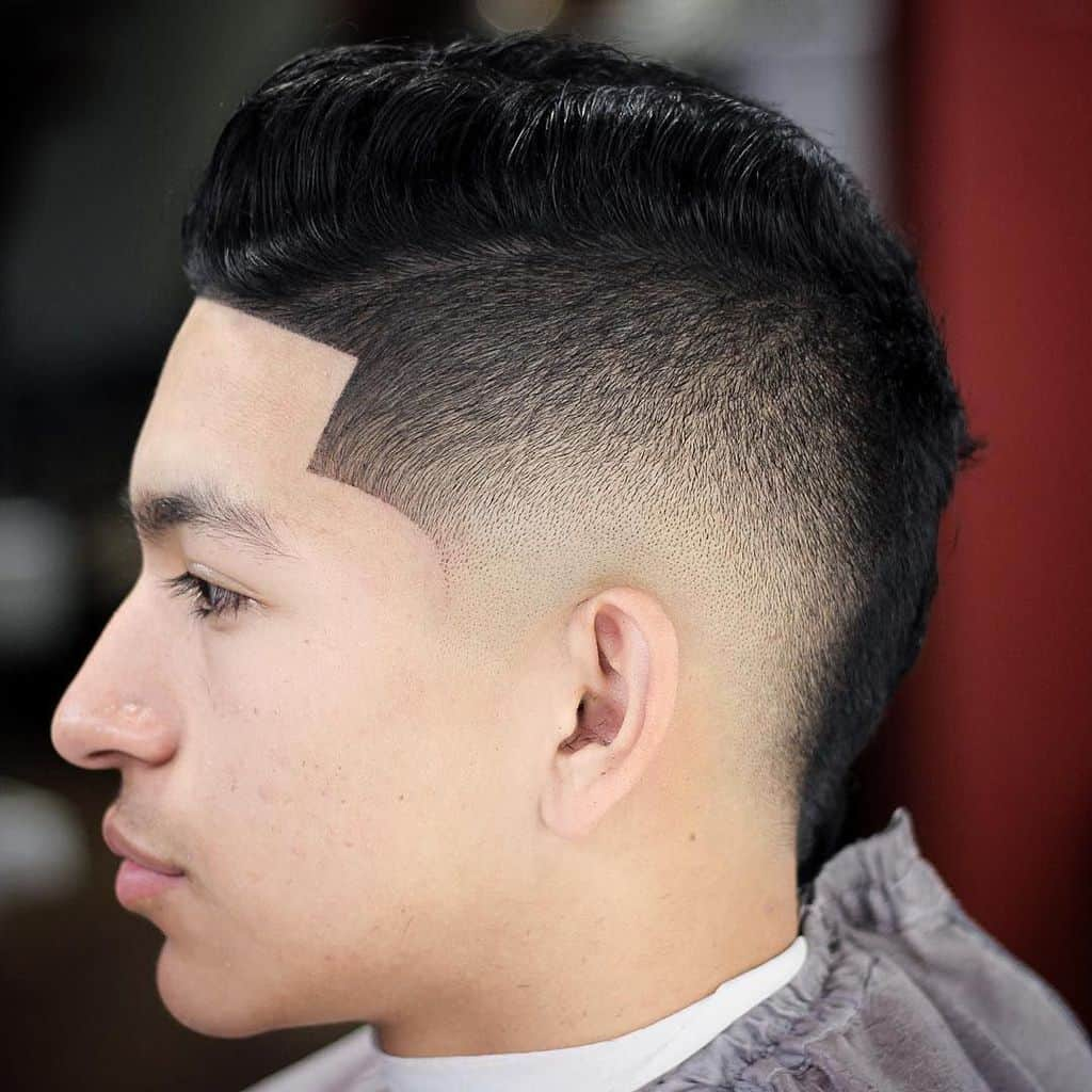 burst fade look with two hair lengths and a low fade. The top long hair is combed to the sides to create a comb-over look