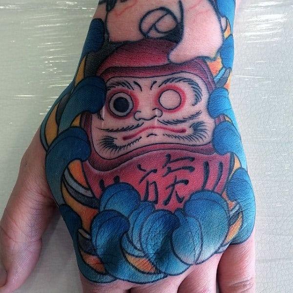 Cool Daruma Doll With Blue Flower Mens Hand Tattoos