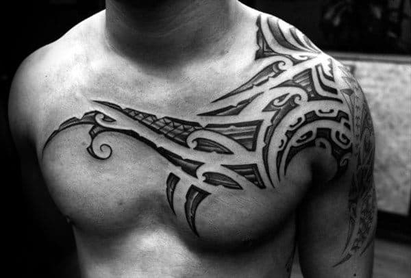 Cool Polynesian Tattoo On Mans Chest And Shoulder With Negative Space Tribal Design