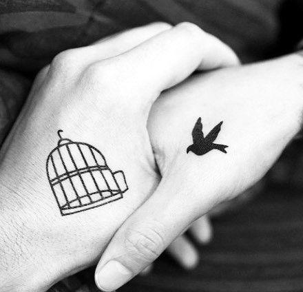 Parejas con tatuajes a juego, pájaro pequeño y jaula en la mano