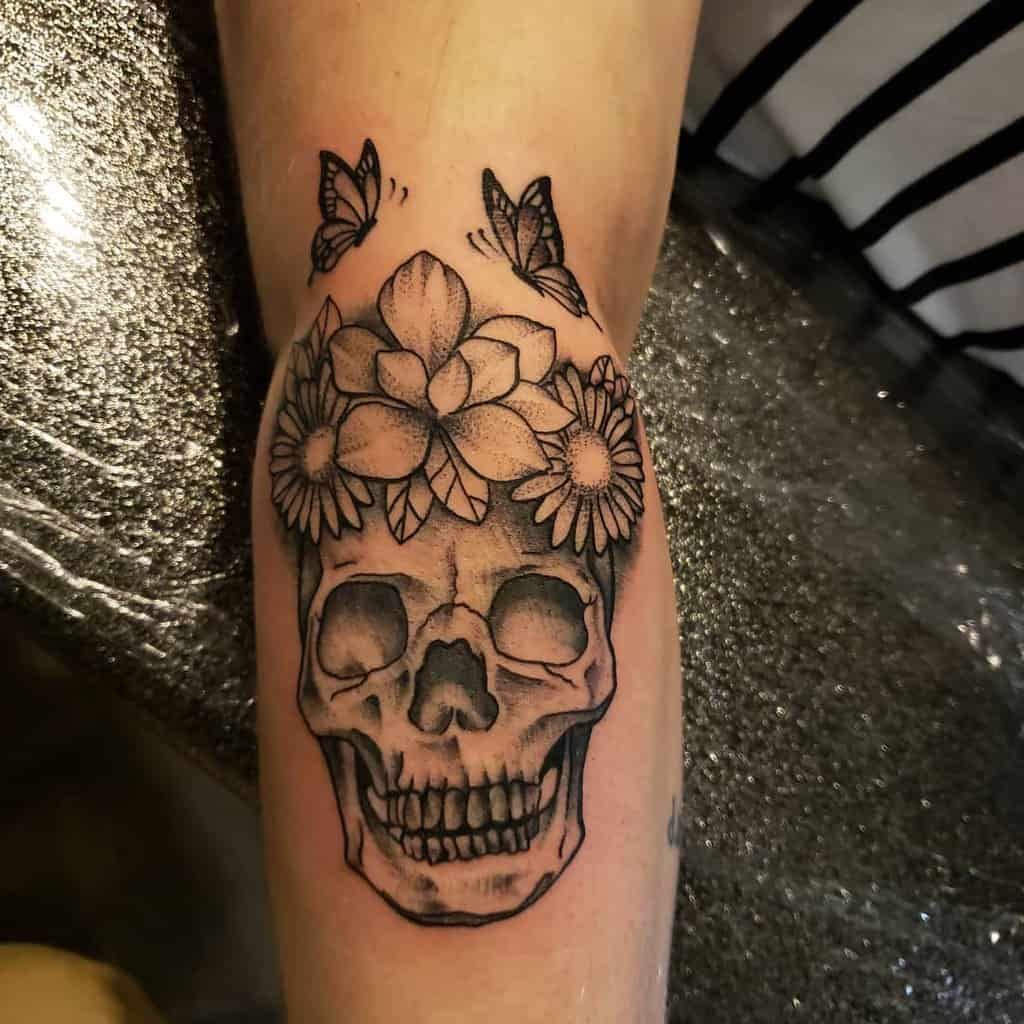 Forearm tattoo black and grey shading skull with crown of daisies and butterflies