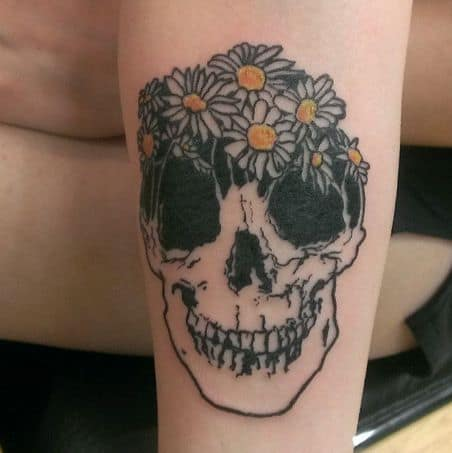 Forearm tattoo black and grey skull with crown of white and yellow daisies