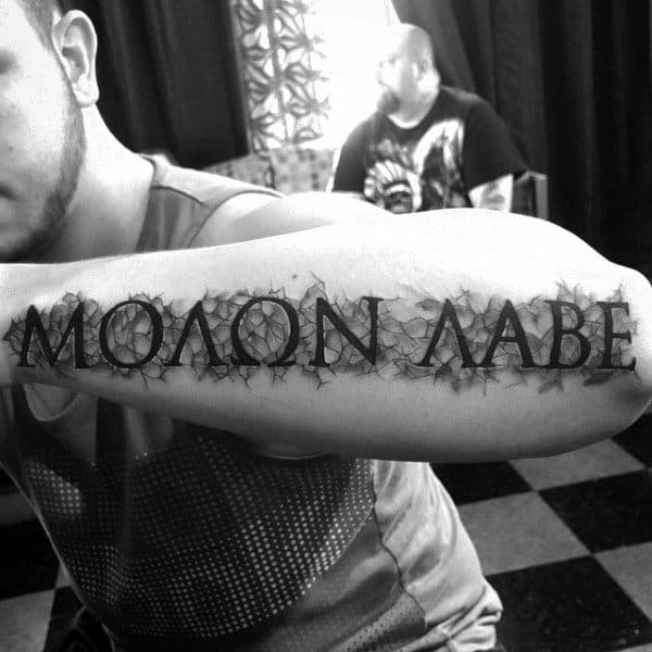 Crushed Stone Black Ink Molon Labe Design Tattoo On Mans Outer Forearm
