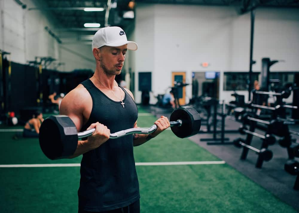 man in a gym performs curl up exercises with a weighted ex bar