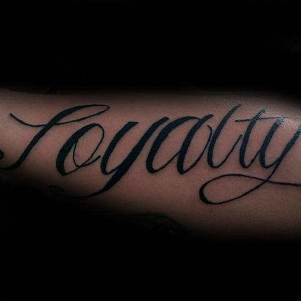 Cursive Loyalty Black Ink Tattoo On Males Outer Forearms