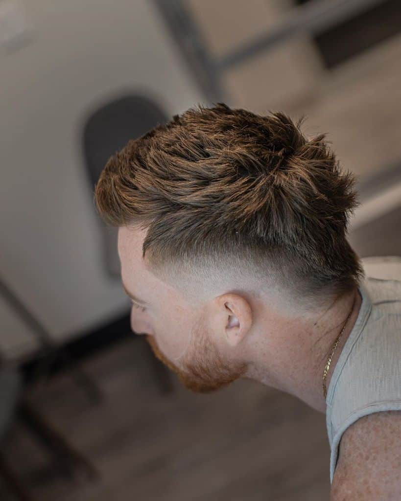 A Mohawk cut with hair extending from front to nape and barely noticeable fading on the sides