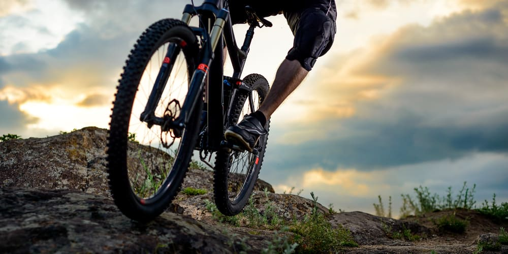 cyclist riding bike on down rocky hill