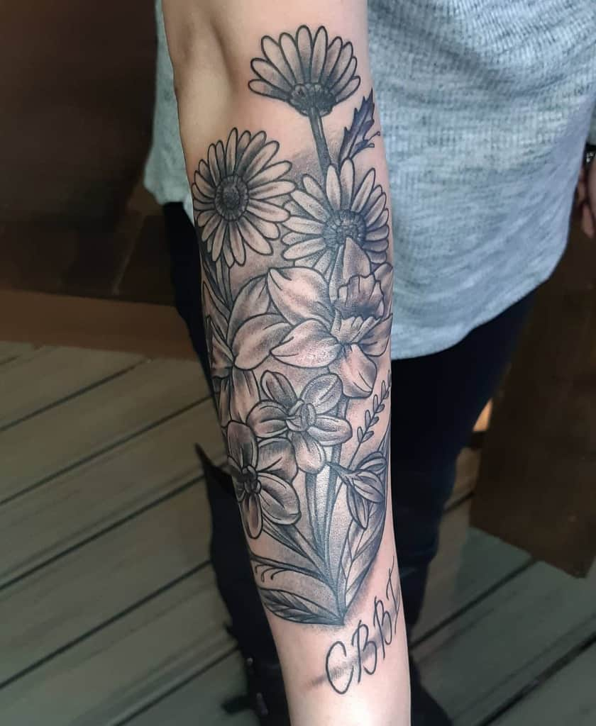 Forearm tattoo large black and grey shading daffodil larkspur daisy with script