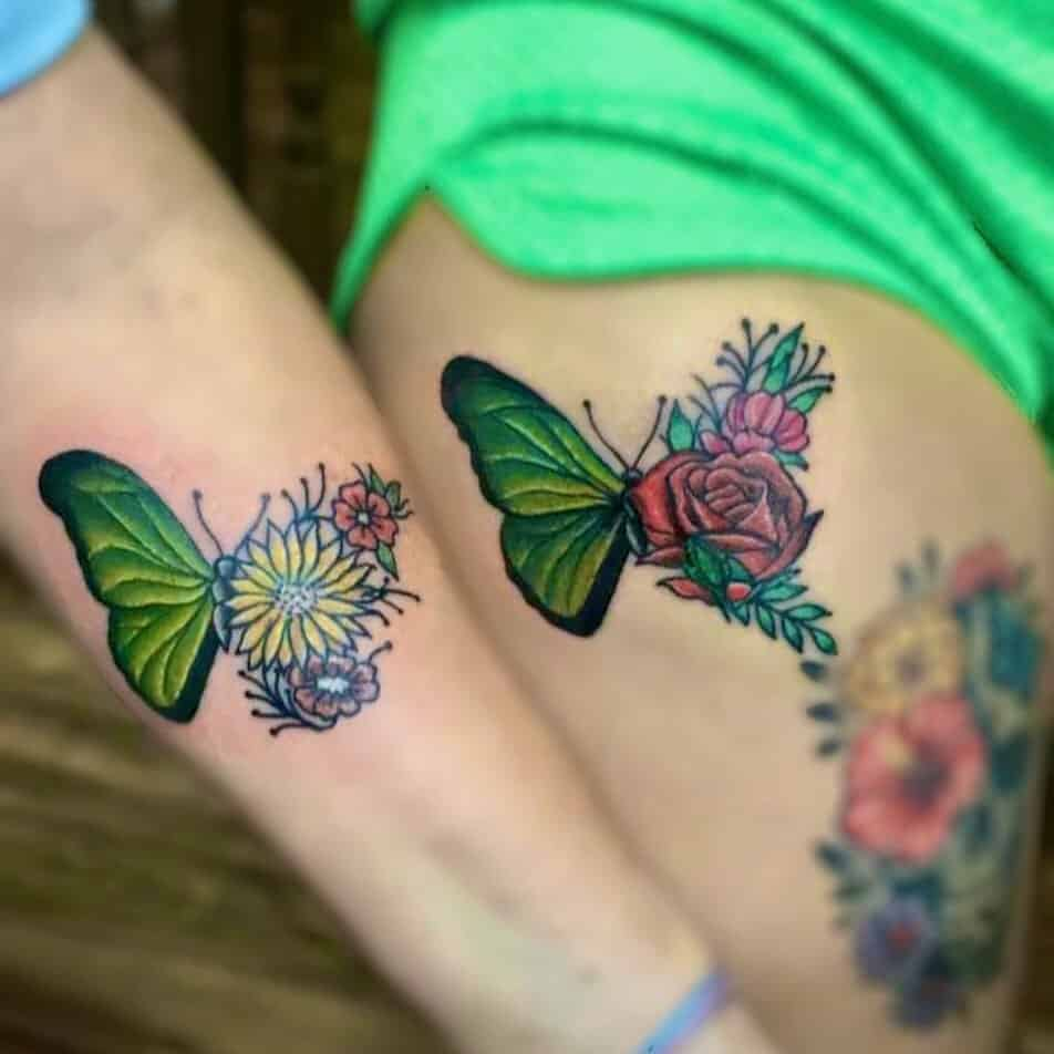 Forearm and thigh tattoos matching color butterflies, daisies and roses