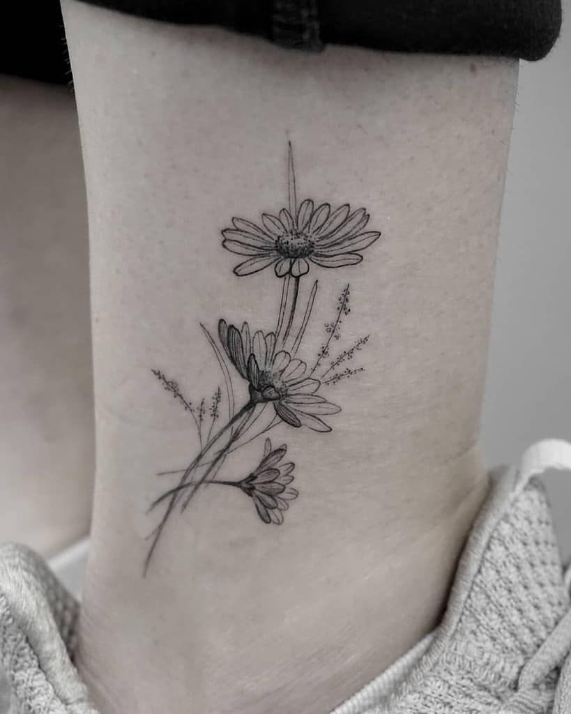 Ankle tattoo black and grey fine line daisy bouquet