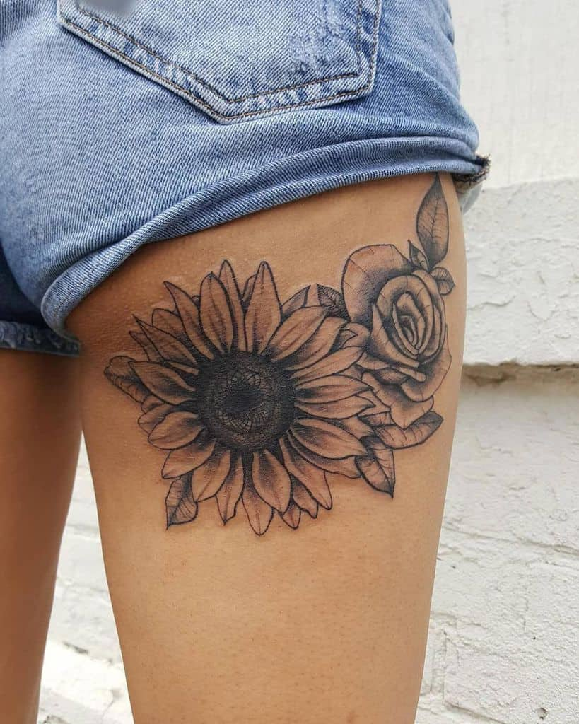 large black and grey tattoo on back of woman's thigh of realistic sunflower and rose with leaves