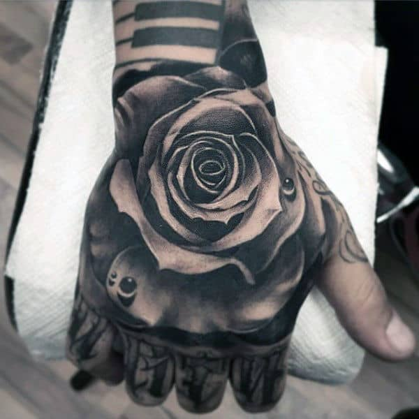 Detailed Mens Hand Tattoo Of Black Ink Rose Flower With Water Droplet