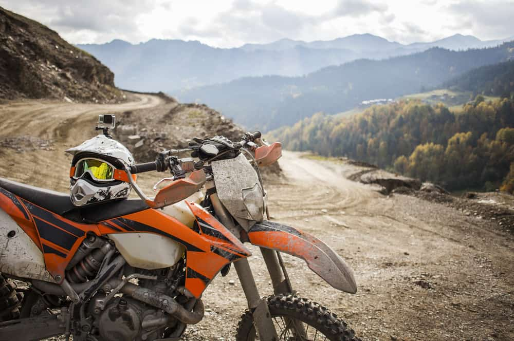 dirty motorcycle with helmet on off road mountain track