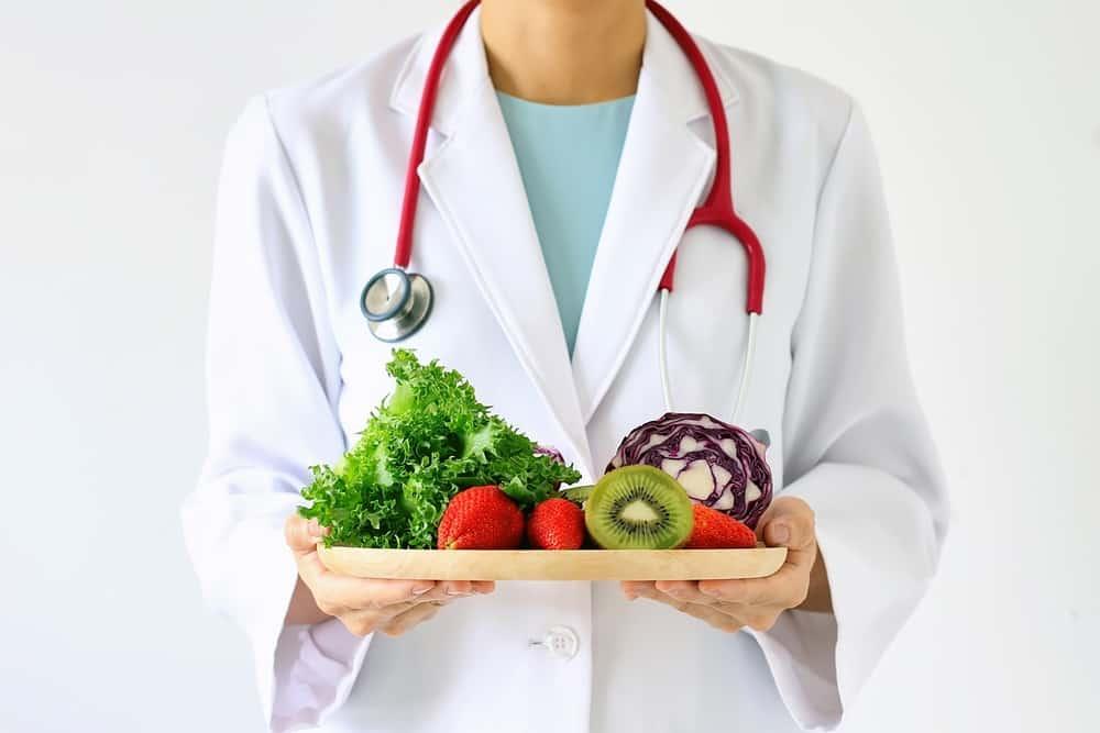 doctor holding fresh fruit and vegetable prescription for good health