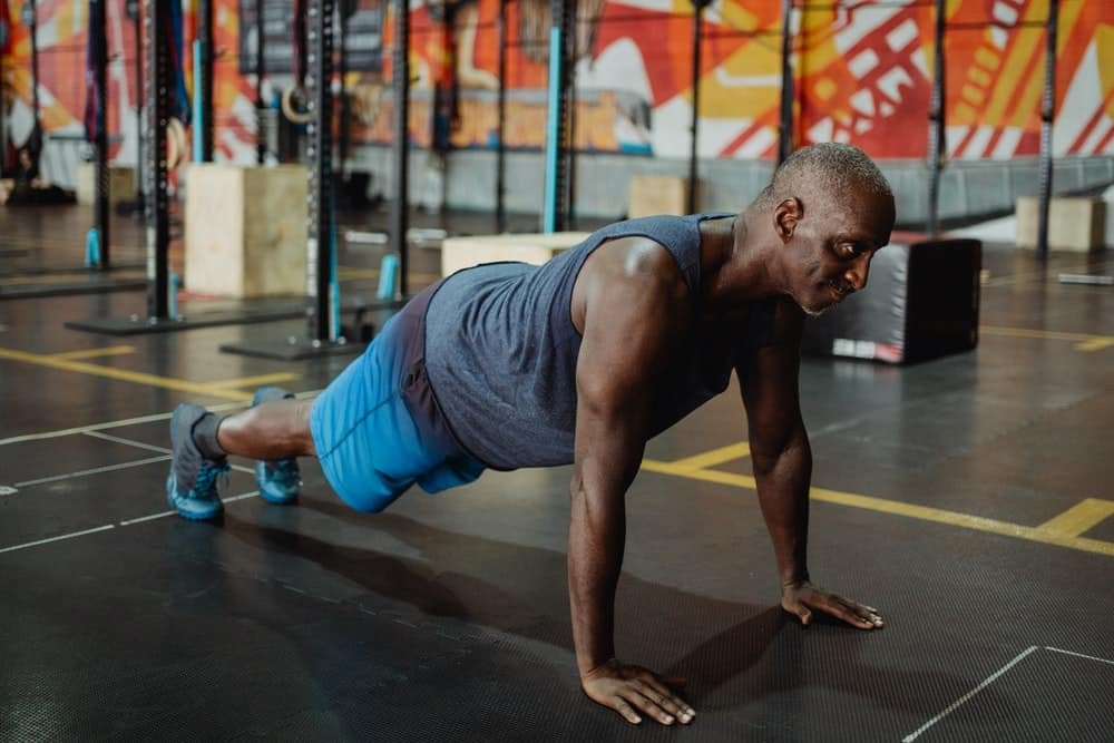 old man in gray tank doing push up on floor in gym