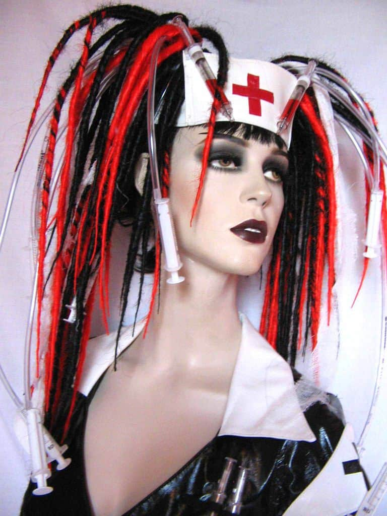 A cyberpunk hairstyle for women with dreadlocks and medical supplies attached to different dreads