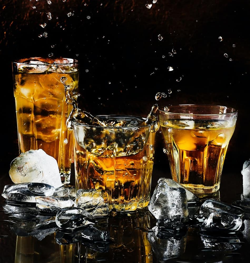 drinking glasses of whiskey with ice cubes