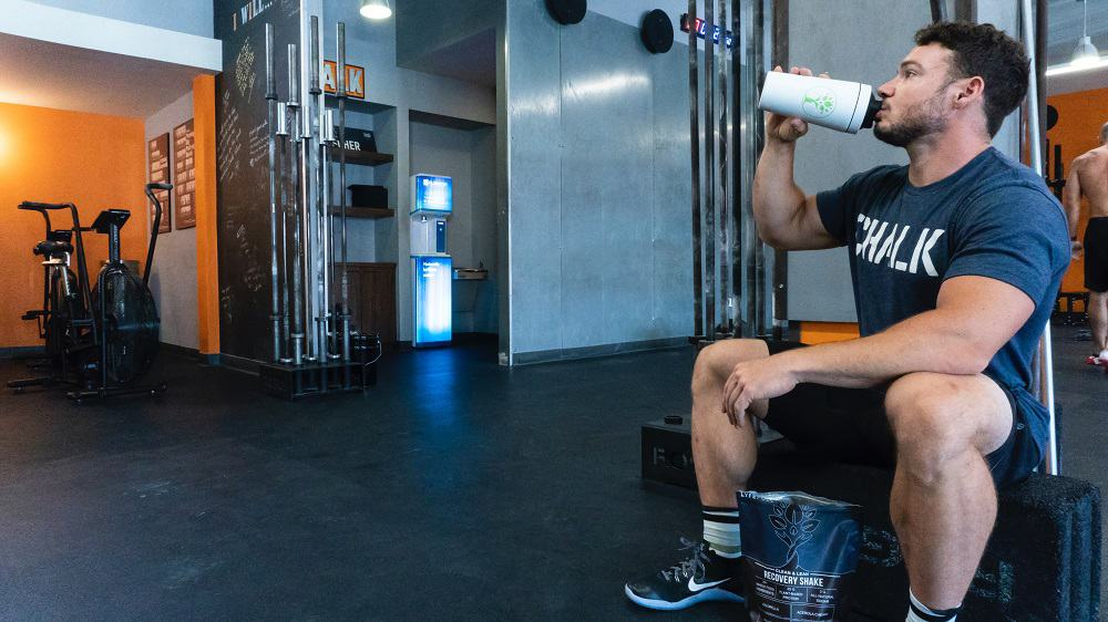 man sits on a bench at the gym, drinking a protein shake from a shaker