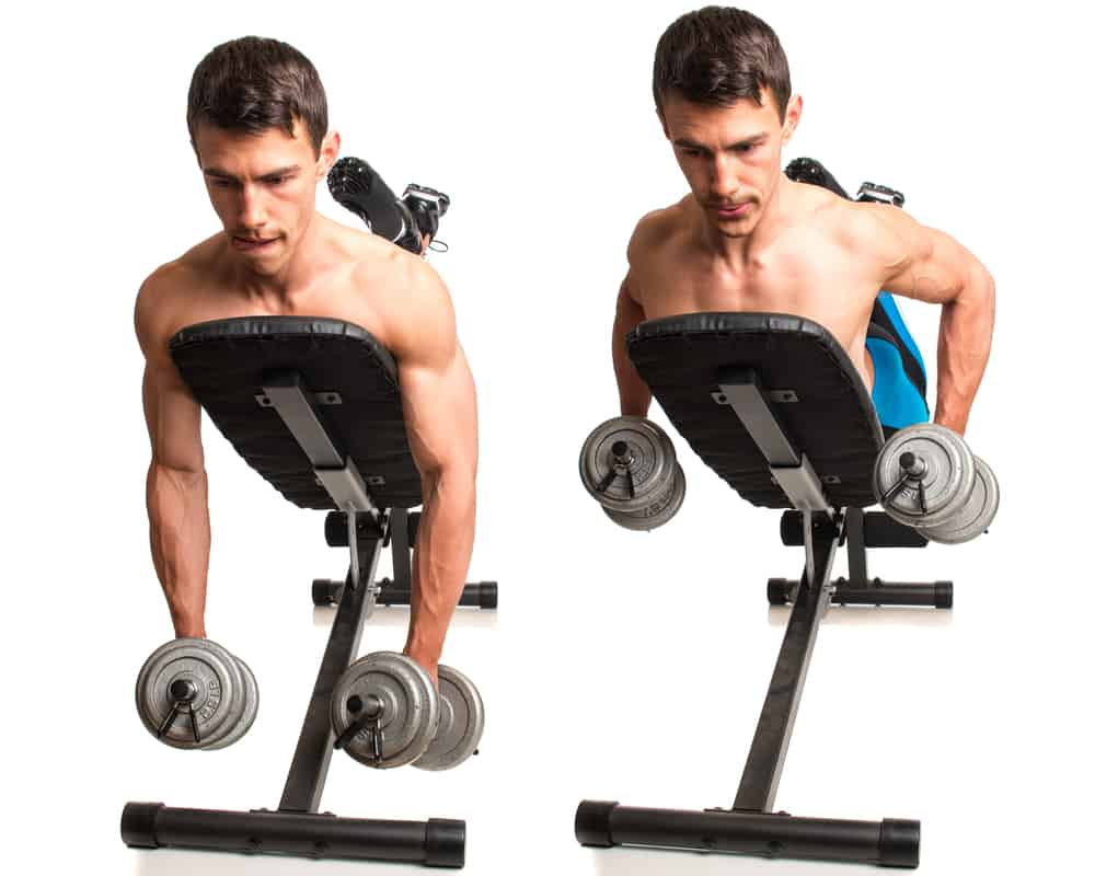 young man doing dumbbell incline row exercise, studio shot