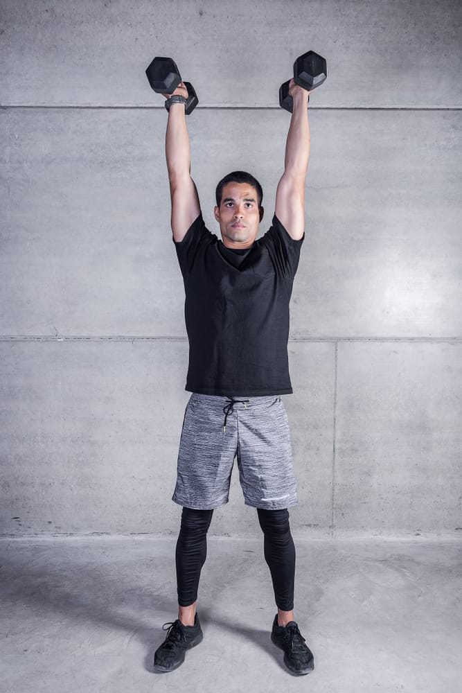 focused young man doing dumbbell overhead carry exercise