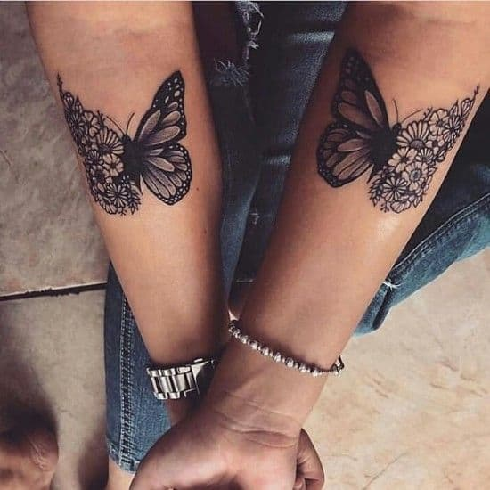 matching black and grey tattoos on two women's forearms of dark butterflies with one floral sunflower wing