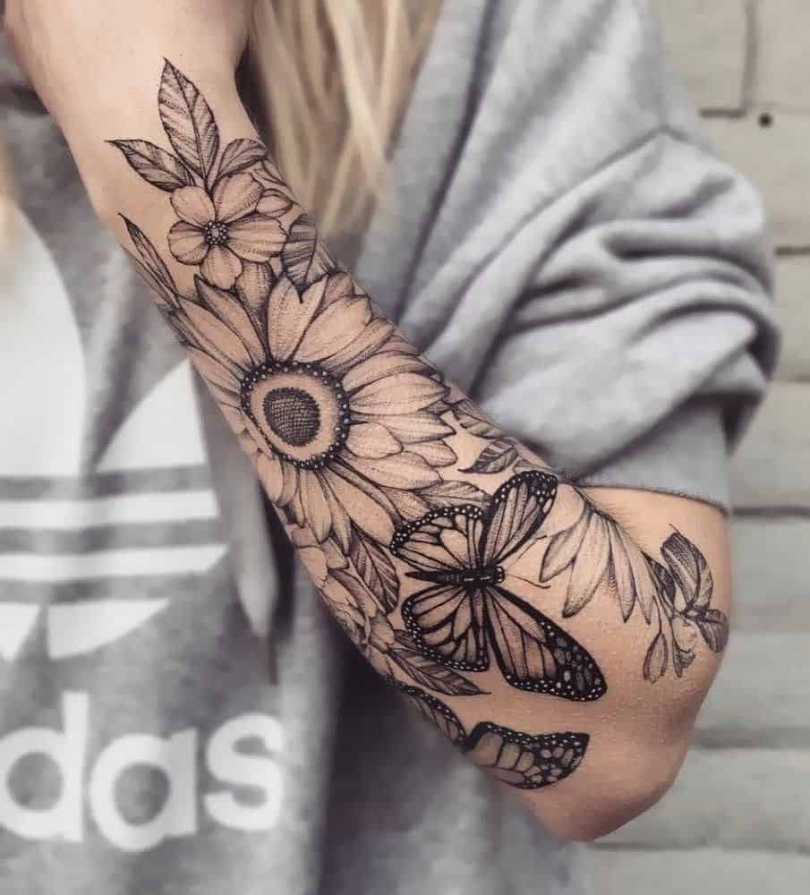 large black and grey half-sleeve tattoo on woman's forearm of realistic bouquet of sunflowers, pansies and butterflies