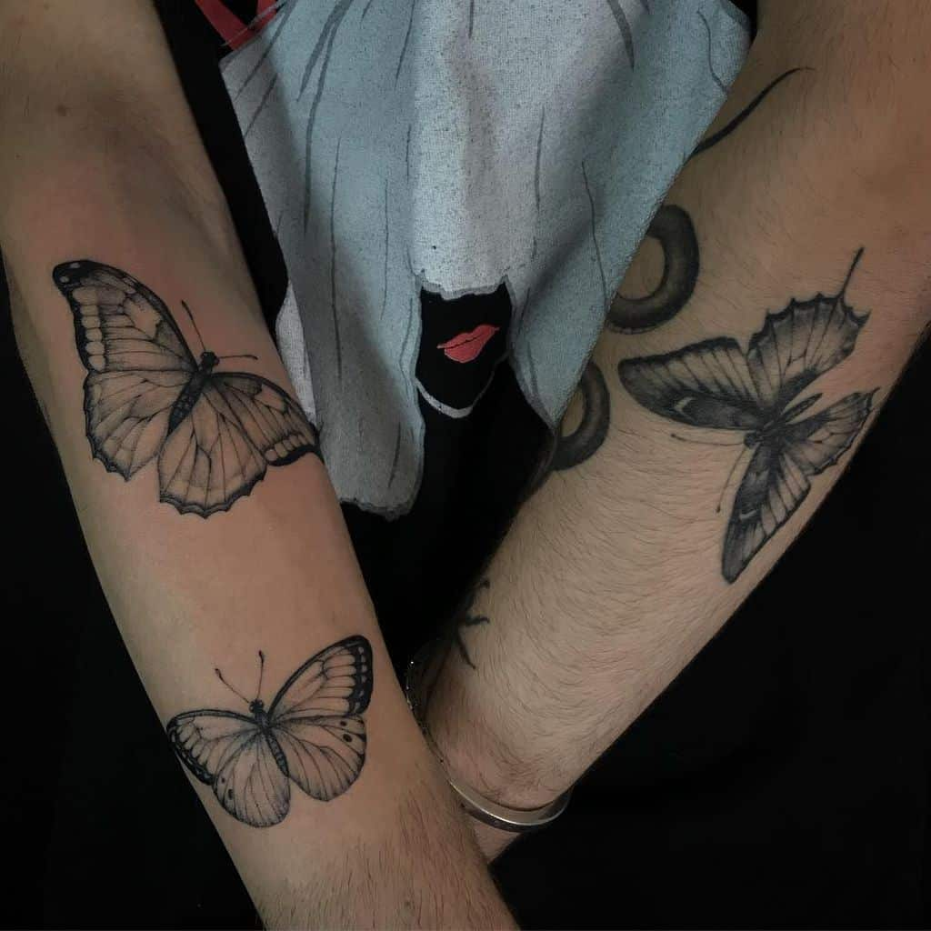 medium-sized black and grey tattoos on man's forearms of three realistic butterflies