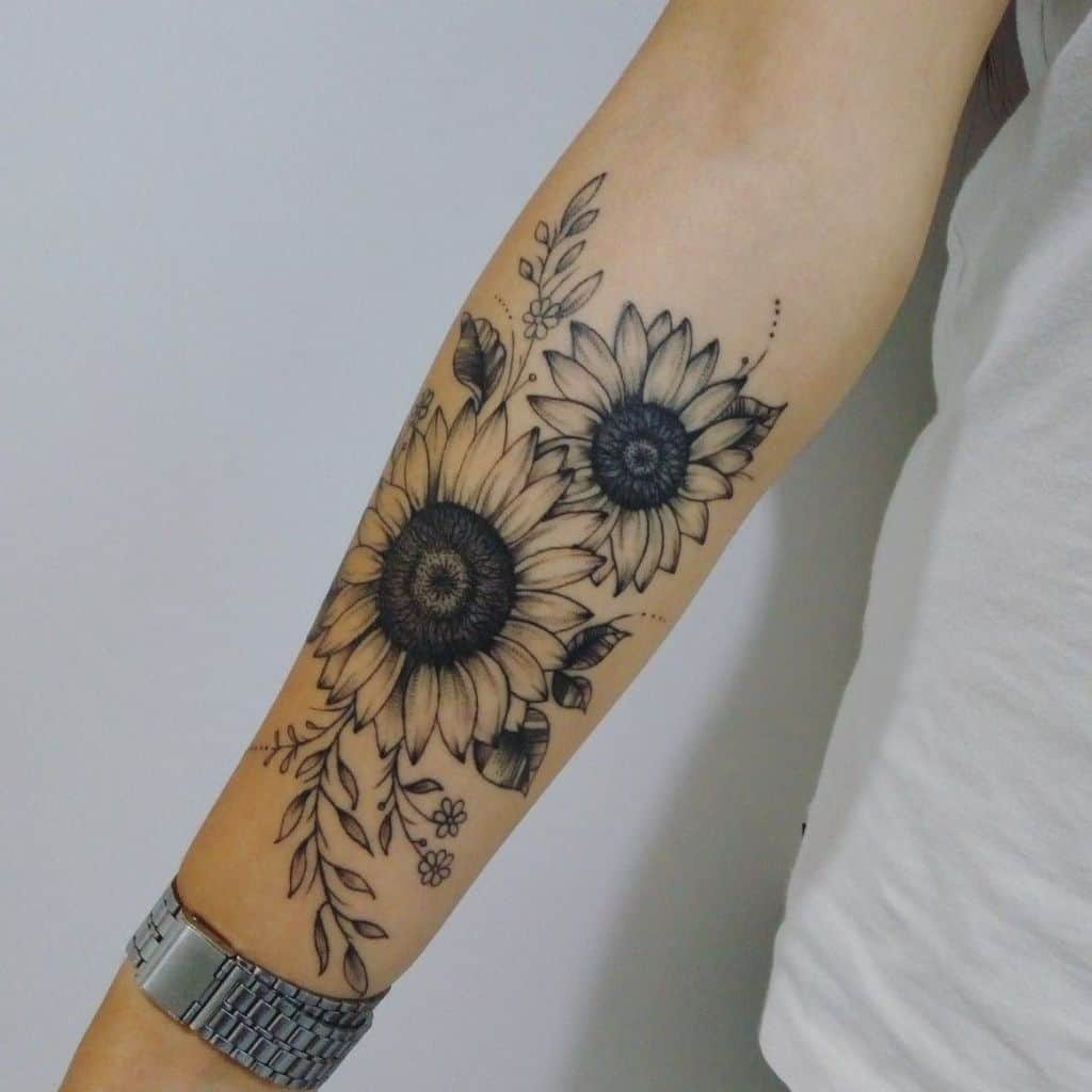 large black and grey tattoo on forearm of a bouquet of two sunflowers with leaves and vines around them