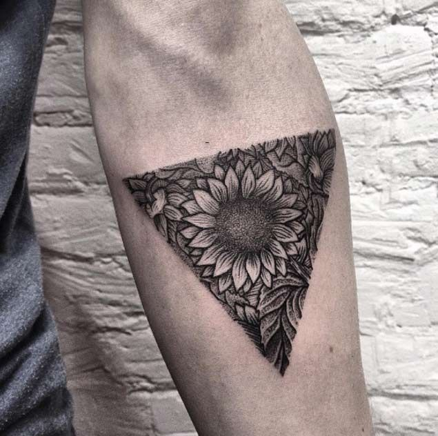 medium-sized black and grey geometric tattoo on man's forearm of a dark realistic sunflower and leaves shaped into a triangle