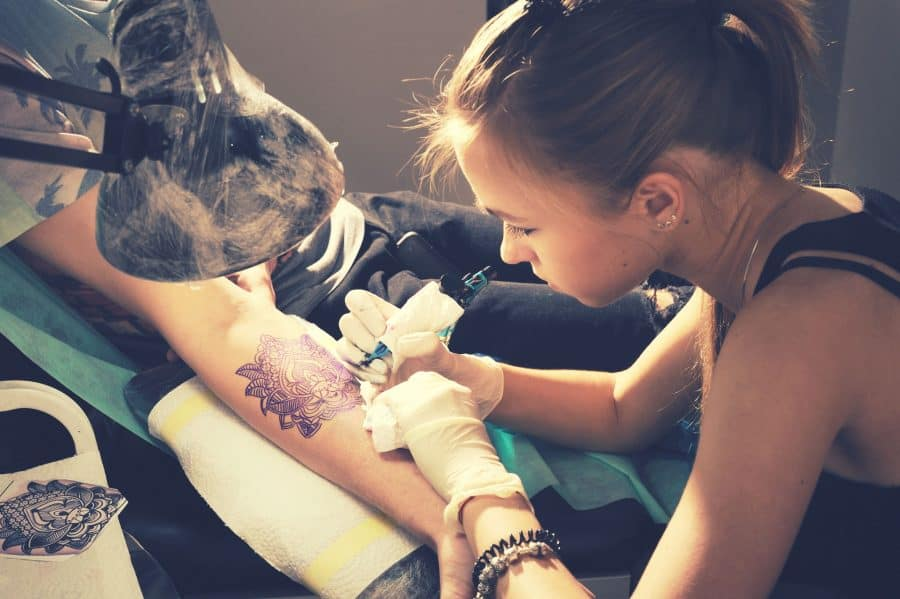 female-artist-working-ink-tattooing-customer