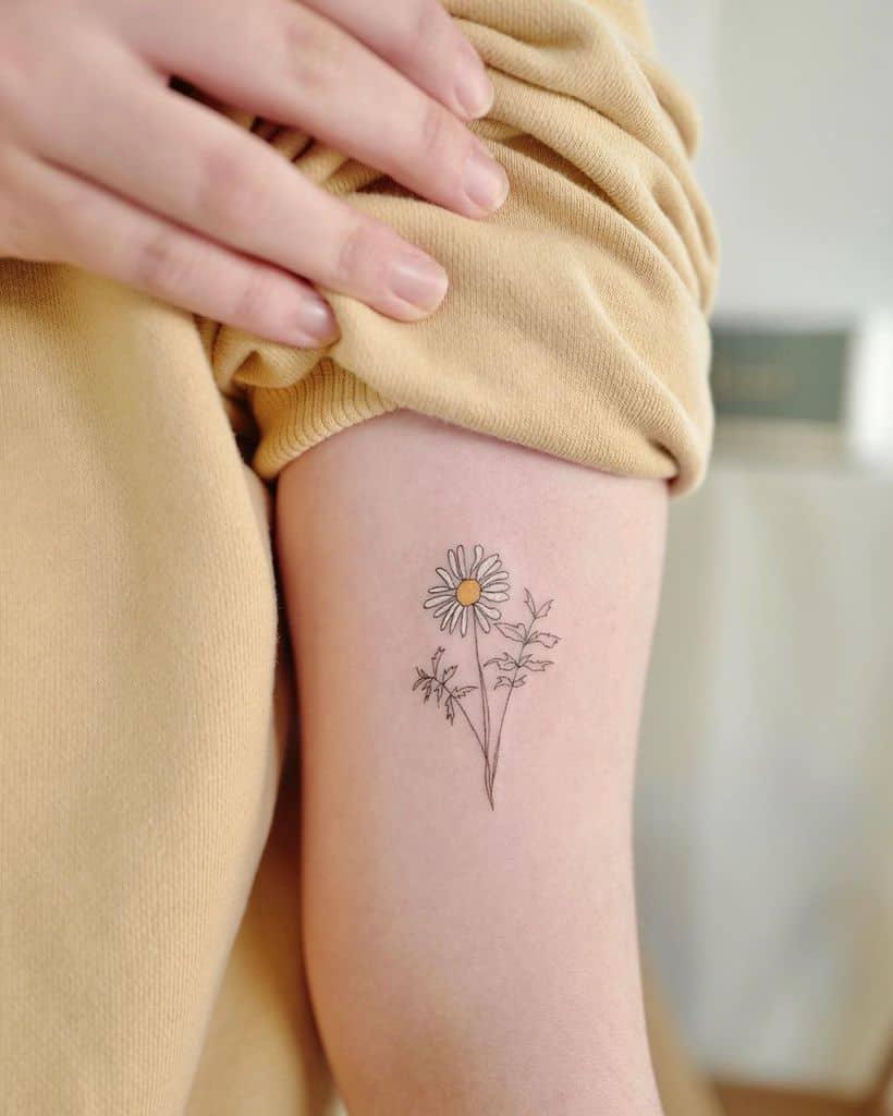 Bicep tattoo fine line color delicate daisy