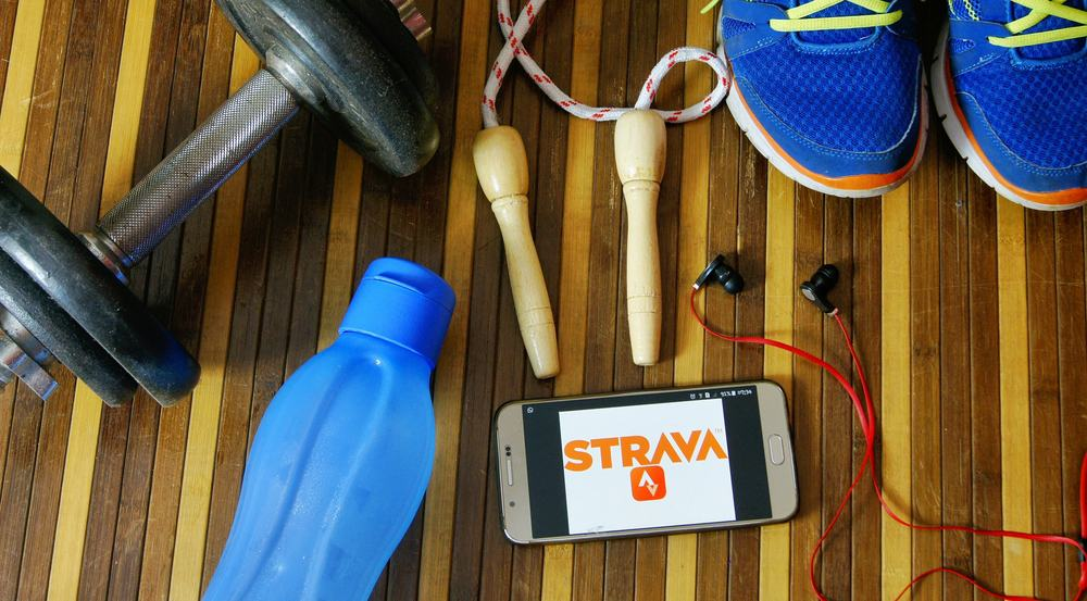 fitness and healthy concept with smartphone using fitness app strava