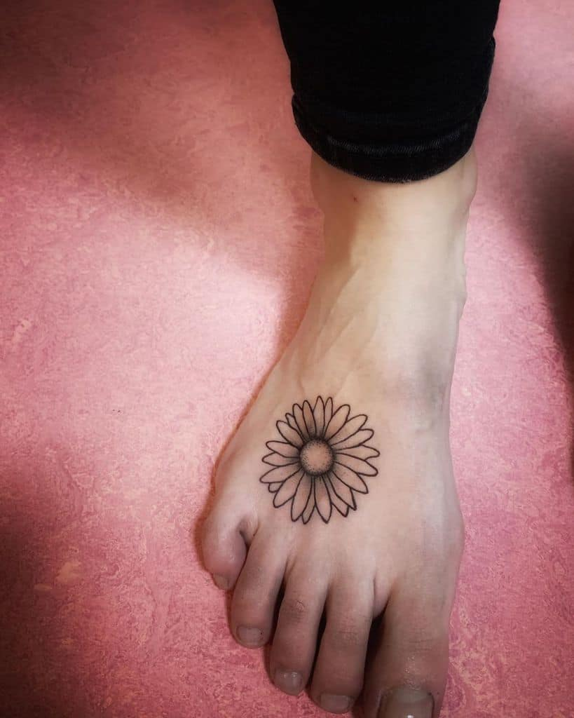 Top of foot traditional black and grey fine line daisy tattoo