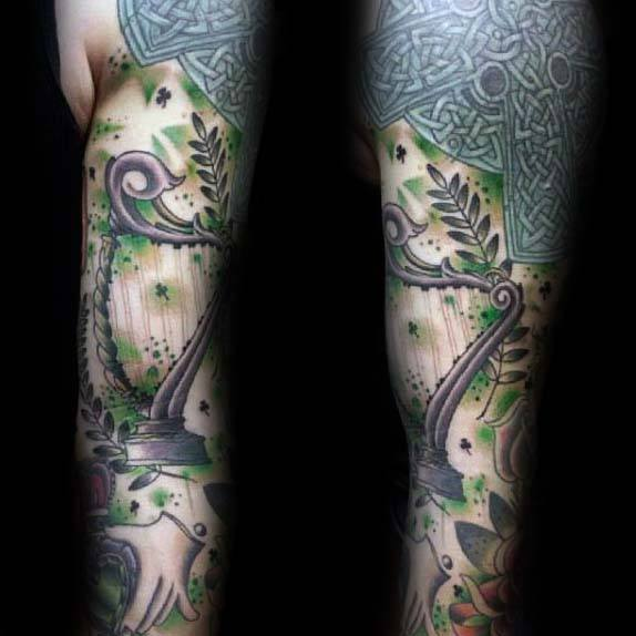 Full Sleeve Irish Themed Tattoo On Man With Harp And Knots