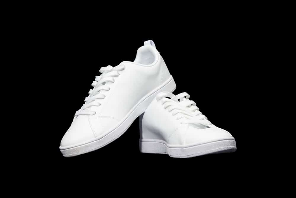 full white sneakers isolated on black background