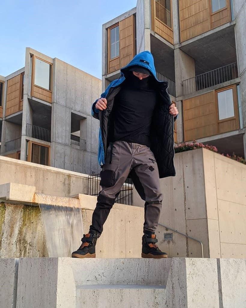 mode futuriste pour homme veste bleue chemise noire pantalon gris