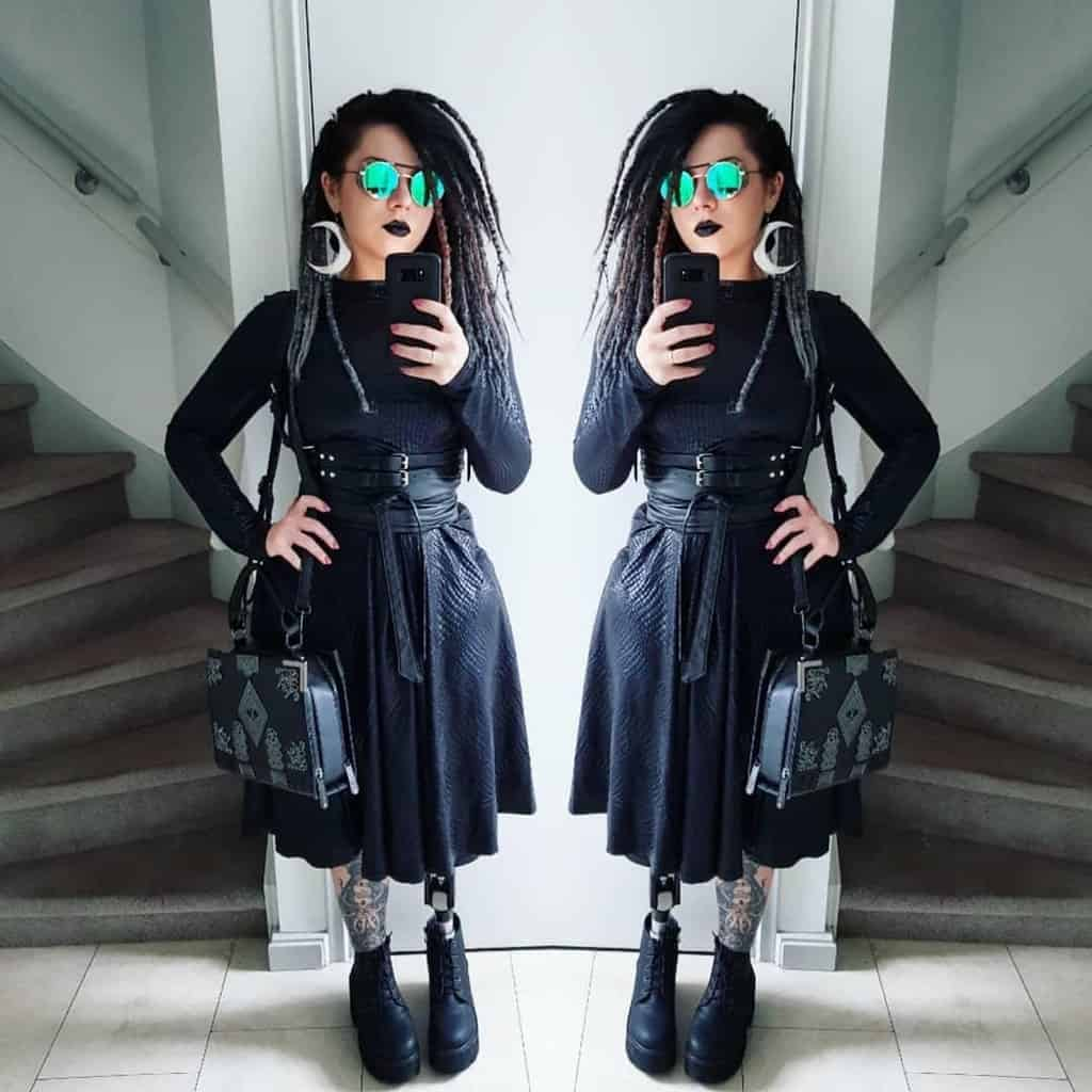futuristic fashion with black long sleeves shirt and skirt and boots