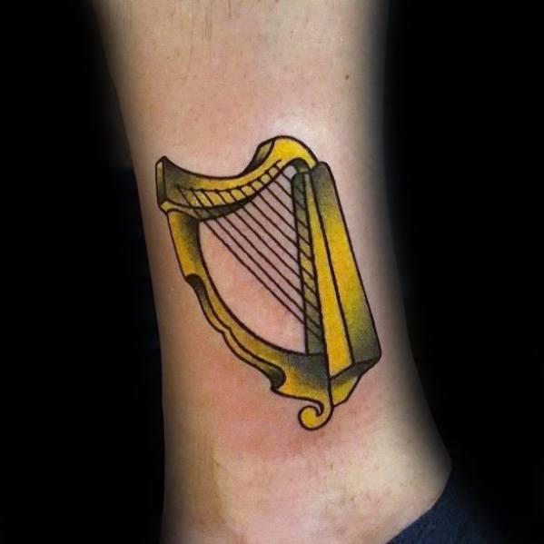 Gentleman With Gold Harp Tattoo On Lower Leg