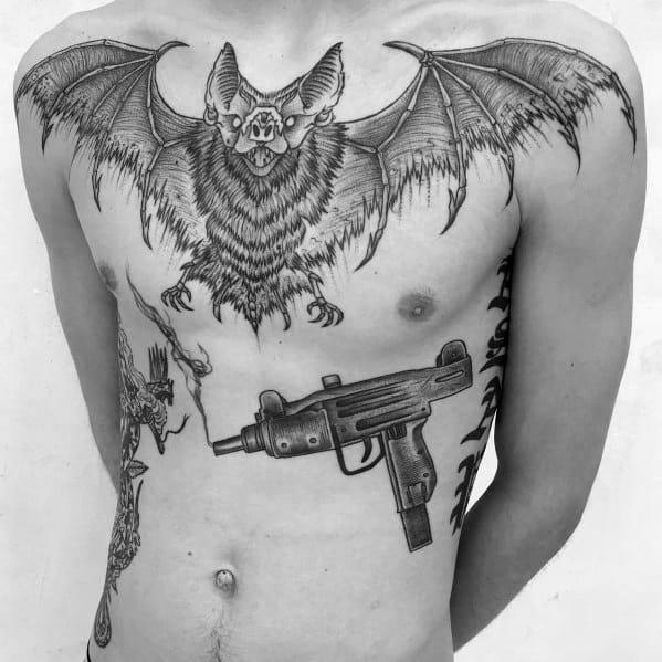 Gentleman With Uzi Tattoo On Ribs