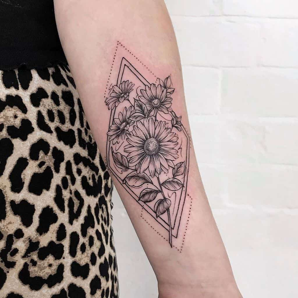 Forearm tattoo black and grey shading geometric shapes framing daisies
