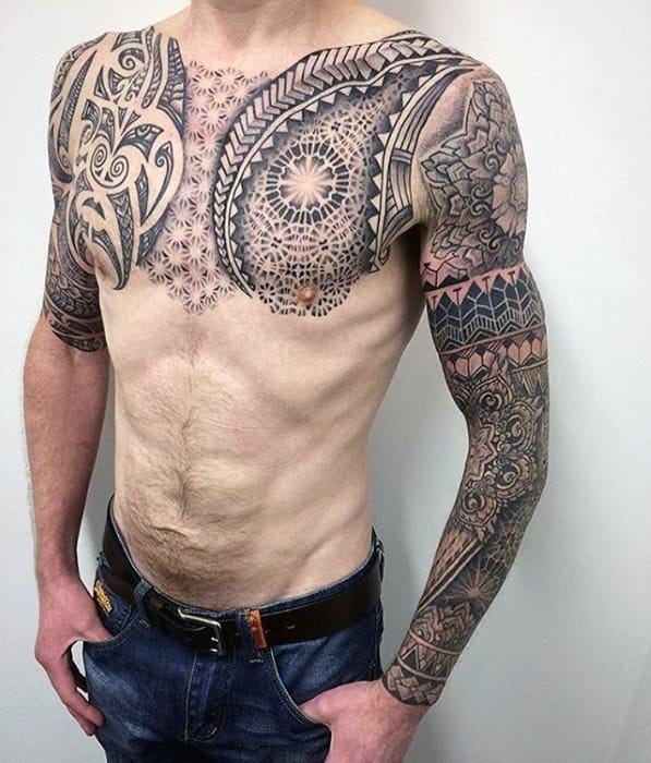 Upper body geometric chest tattoo featuring tribal designs on man's chest and upper arms