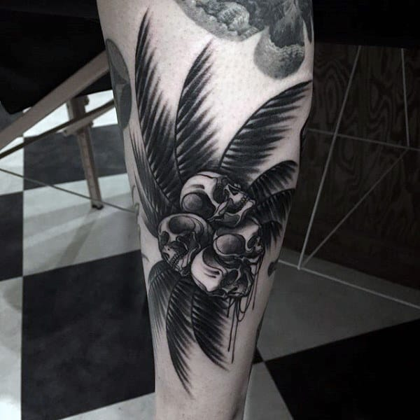 Ghastly Skulls On Palm Tree Tattoo On Legs For Men