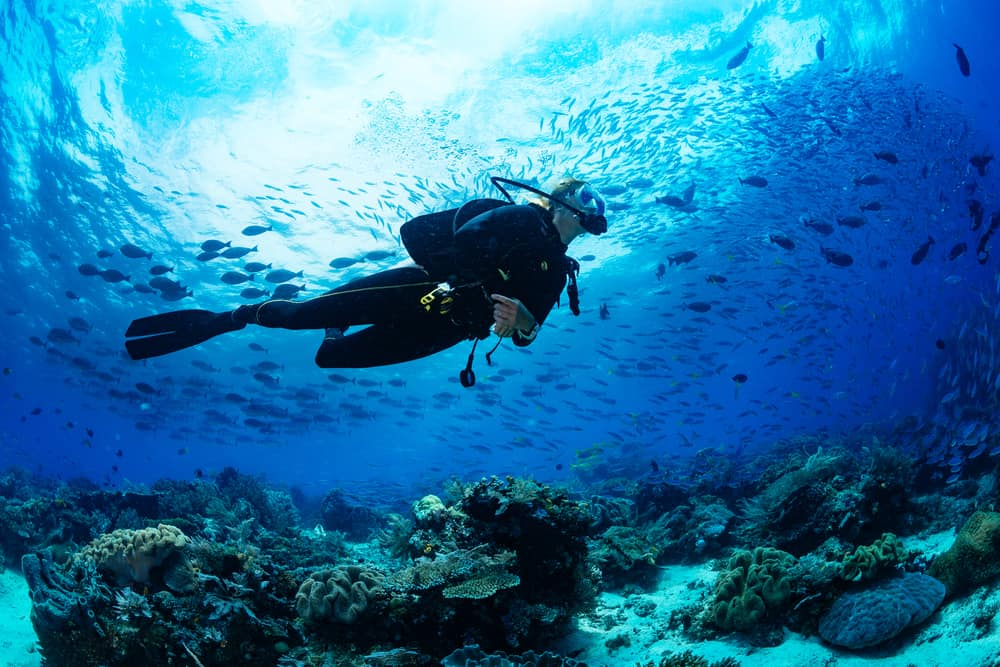 girl scuba diver on tropical reef