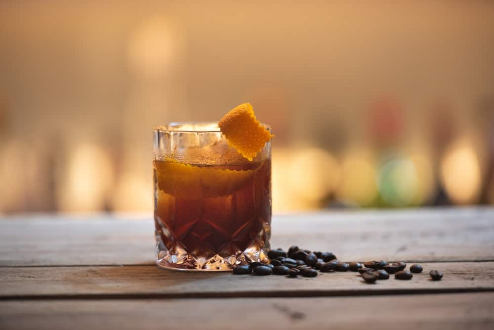 full glass of rum on wooden table
