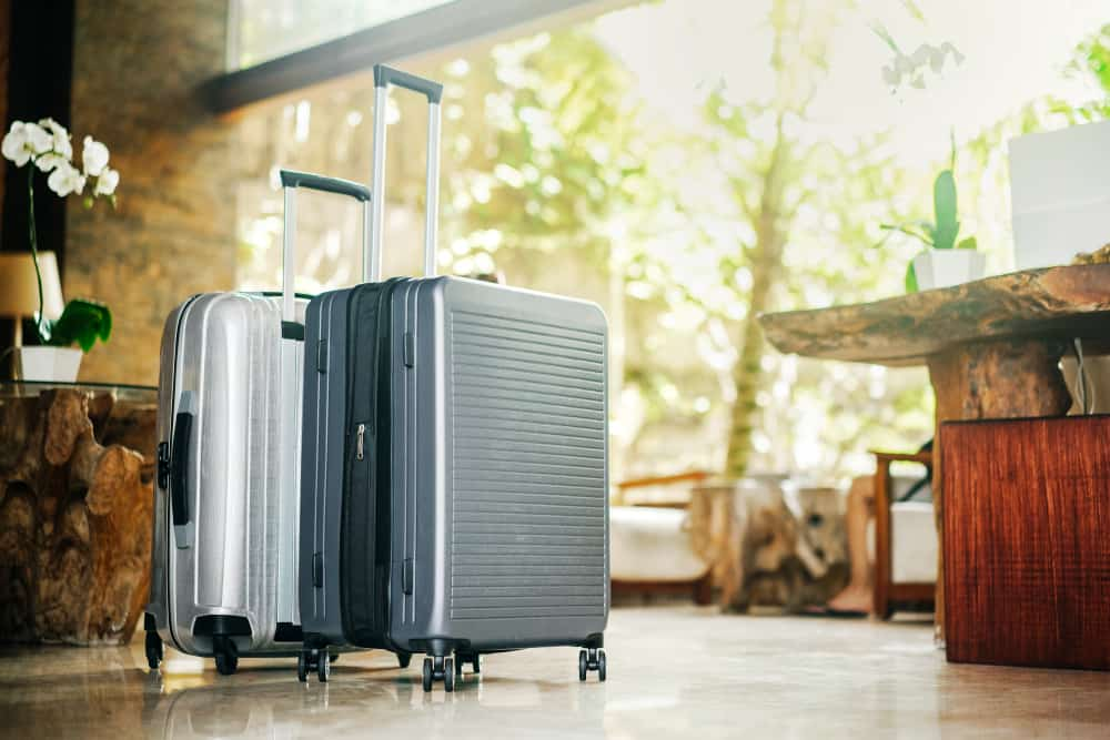 gray large suitcases stand in the lobby of the hotel