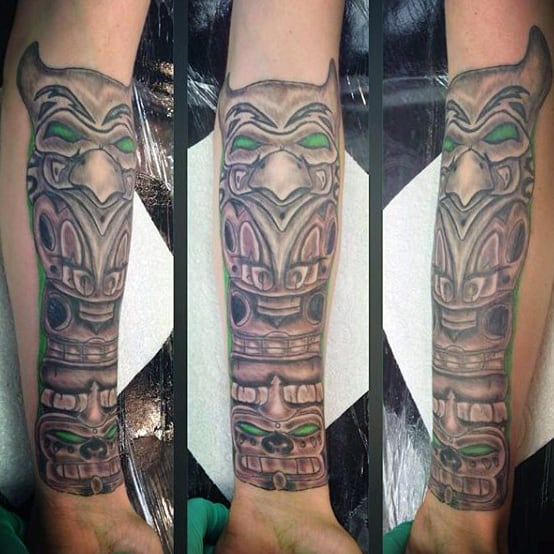 Green Outlined Traditional Totem Pole Tattoo On Gentleman