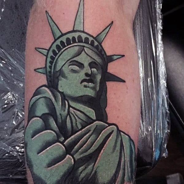 Green Statue Of Liberty Clenching Fish Mens Tattoo
