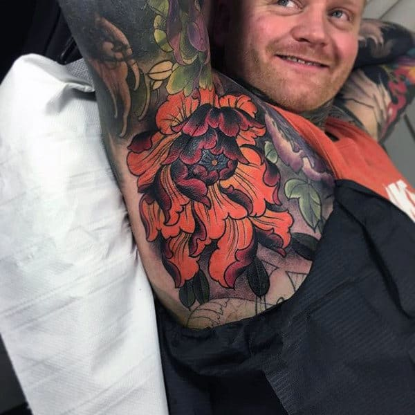 Guy With Bright Orange Florals Tattoo On Armpits