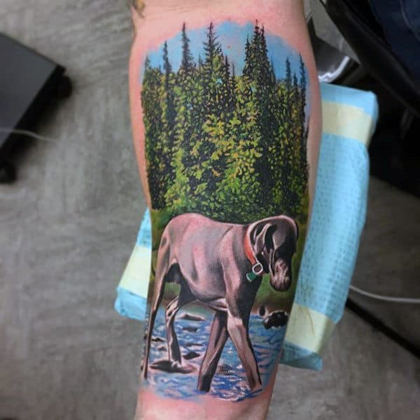 Guy With Colorful Tattoo Of Dog Wading Through Stream On Forearm
